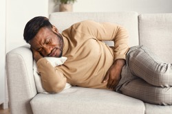 Stomachache. Afro Man Suffering From Abdominal Pain Touching Aching Stomach Lying On Couch At Home