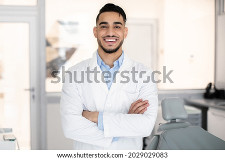 Stomatologic Services. Portrait Of Smiling Arab Dentist Doctor In Uniform Posing In Modern Clinic Interior, Professional Middle Eastern Stomatologist Standing With Folded Arms And Smiling At Camera Foto stock ©