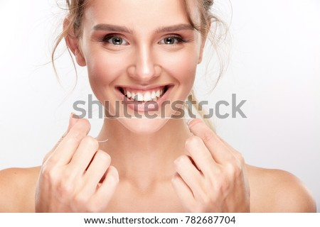 Stomatology concept, head and shoulders of woman with strong white teeth looking at camera and smiling, holding teeth thread. Young woman at dentist's, studio, indoors