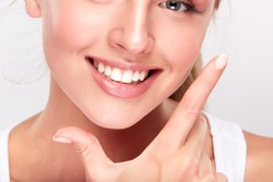 Stomatology concept, partial portrait of girl with strong white teeth looking at camera and smiling, fingers near face. Closeup of young woman at dentist's, studio, indoors