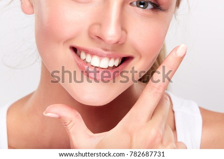 Stomatology concept, partial portrait of girl with strong white teeth looking at camera and smiling, fingers near face. Closeup of young woman at dentist's, studio, indoors #782687731