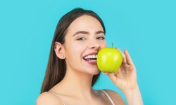 Stomatology concept. Woman with perfect smile holding apple, blue background. Woman eat green apple. Portrait of young beautiful happy smiling woman with green apples. Healthy diet food.