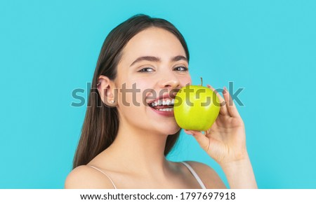 Stomatology concept. Woman with perfect smile holding apple, blue background. Woman eat green apple. Portrait of young beautiful happy smiling woman with green apples. Healthy diet food. ストックフォト ©