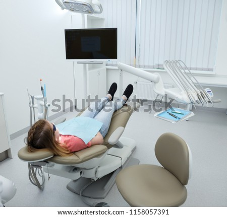 Stomatology interior of  modern dental clinic with professional chair. Dentistry, medicine, medical equipment and stomatology concept. Patient is sitting in the chair