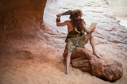 Stone Age luddite caveman scratching his head with a club while looking at his stone tablet outdoors in a weathered rock cave
