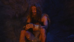 Stone-age neanderthal wildman discovering smartphone future technology sitting amused at bonfire with ancient family of hunter-gatherers. Night in the cave.