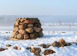 Stone altar near the frozen river in cold sunny winter morning.