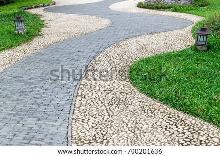 stone and brick walkway pavement in garden pass through grass field with two lamp lighting on ground beside the way