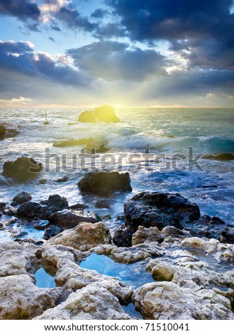 Stone and storm sea during sundown. Natural composition