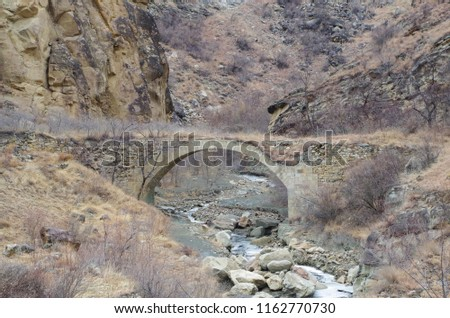 Stone arch bridge and the river. Nature and travel. Russia, North Caucasus, Dagestan, Shamilsky District