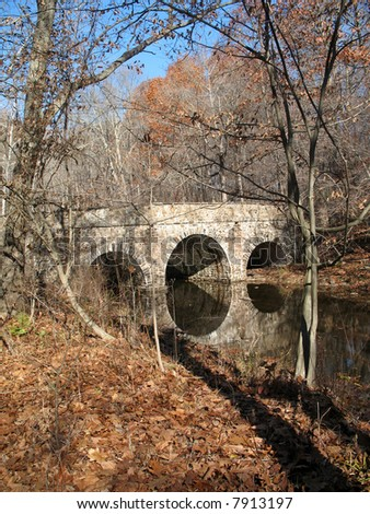 Stone arch bridge is reflected in slow moving stream . - stock photo