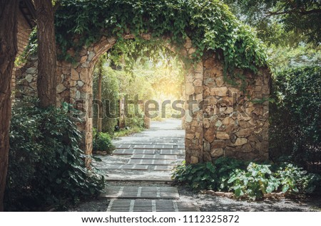 Stone arch entrance wall with ivy in the garden.