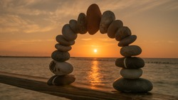 Stone arch with a red stone at the top, at sunset on a beach. Mediate, balance and stability Concept.