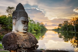 Stone Asura on causeway near South Gate of Angkor Thom in Siem Reap, Cambodia. Beautiful sunset over ancient moat in background. Mysterious Angkor Thom is a popular tourist attraction.