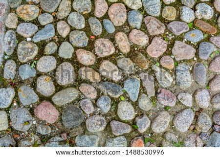 Stone background of pavement with rough granite boulders with little bit grass and moss. Texture of historic medieval cobble paving is laid on the city street