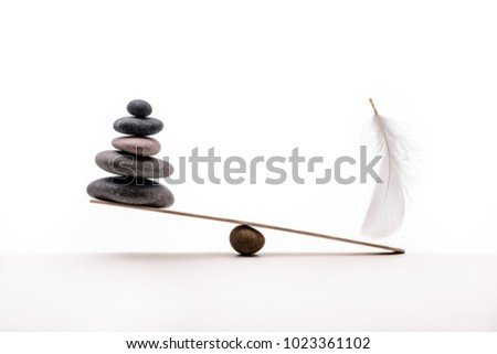 Stone balance with plume. Concept of heavy and light.