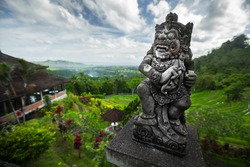 Stone balinese statue with green lush valley on the background. Bali island, Indonesia