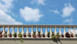 Stone balustrade of a balcony with flowers between the columns. Blue sky with fluffy clouds on background. Copy space