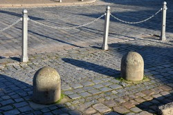 stone barriers in a square shaped cylinder with a hemisphere on top. granite curbs as stops at the parking lot. chain decorative fence against a colony of pedestrians and vehicles with a metal bollard