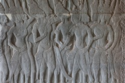 Stone bas-relief with human figures in Angkor Wat temple, Siem Reap, Cambodia. Male figures stone carving on ancient temple wall panel. Cambodian traditional art and craft. Tourist sightseeing photo