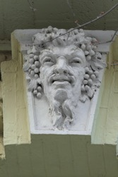 Stone bas-relief with the head of the Greek god. Instead of hair a bunch of grapes