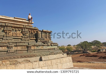 Stone bas-reliefs on the walls in Temples Hampi. Carving stone ancient background. Carved figures made of stone. Unesco World Heritage Site. Karnataka, India. A girl is sitting on top of a mountain.