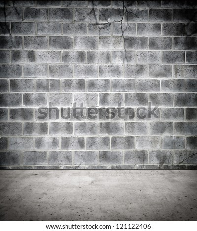 Stone block wall with tree twigs and concrete floor - stock photo