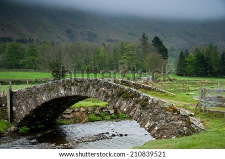 Stone bridge crosses a stream in the English Lake District