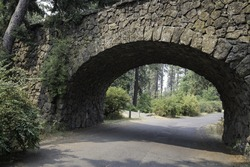 Stone bridge for pedestrians in a park surrounded by greenery