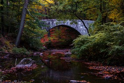 Stone bridge in Rockefeller State Park over the Pocantico River in autumn