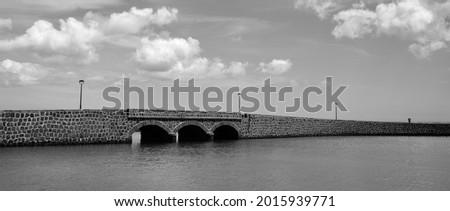 Stone bridge in the sea, coast of Arrecife, Lanzarote, Canary Islands, monochrome mode Foto stock ©