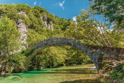Stone Bridge of Kleidonia.  This stone bridge with its unique arch is situated near the village of Kleidonia at the end of Vikos Gorge in Zagori, Epirus, Greece. Old Arch Bridge over Voidomatis River.