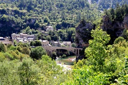 Stone bridge of Saint Chély du Tarn with single vault and carrying a road with single access to the village, surrounded by the causse forests of the Tarn valley in France.
