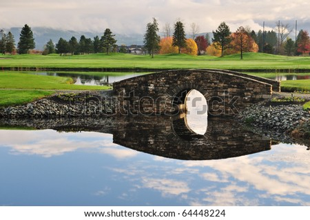 Stone bridge over creek on golf course with autumn colors