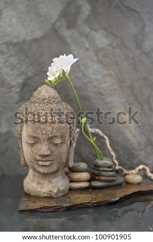 Stone Buddha head sculpture with flower and stones in water.