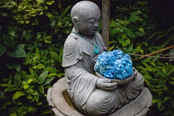 Stone Buddhist Statue in Nature Forest Setting Holding Offering of Blue Flower Pedals (Kamakura, Japan).