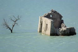 stone building surrounded by water, destroyed by flooding