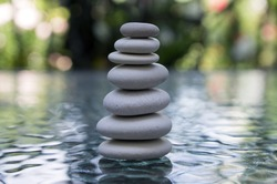 Stone cairn on green blurry background, light pebbles and stones