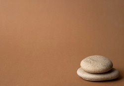 Stone cairn on striped brown background, five stones tower, simple poise stones, simplicity harmony and balance, rock zen sculptures side view