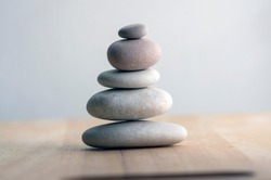 Stone cairn on striped grey white background, five stones tower, simple poise stones, simplicity harmony and balance, rock zen sculptures
