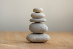 Stone cairn on striped grey white background, five stones tower, simple poise stones, simplicity harmony and balance, rock zen sculpture