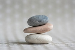 Stone cairn on striped grey white background, three stones tower, simple poise stones, simplicity harmony and balance, rock zen sculpture