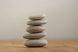 Stone cairn on wooden background, five stones tower, simple poise stones, simplicity harmony and balance, rock zen sculpture