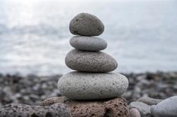 Stone cairn tower, poise stones, rock zen sculpture, light grey pebbles