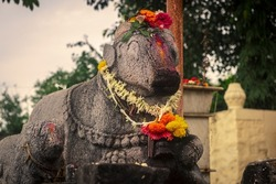 Stone carved idol of nandi bull, lord Shiva hindu temple decorated with flowers and colors