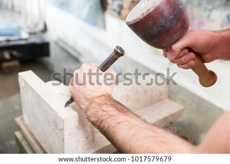 Stone carver working with hammer and chisel at marble column