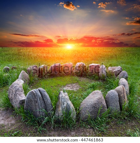 stone circle on green meadow against sunset background