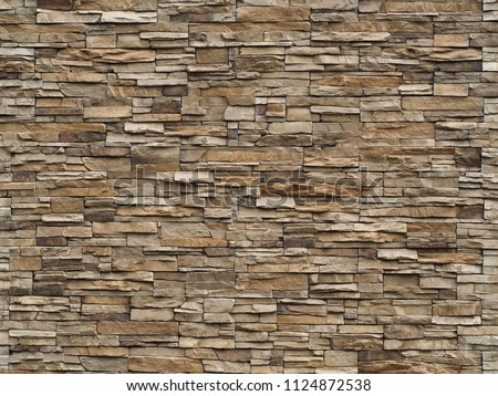 Stone cladding wall made of  striped stacked slabs of natural brown rocks. Panels for exterior . stock photo
