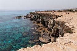 Stone coastline of the Ayia Napa bay. Cyprus stone cliffs. Cyprus waterfront. Clear blue sea in Asia Napa.