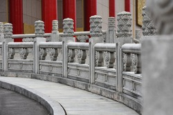 Stone column pillars in typical ancient asian art and traditional hand rails with beautiful flower ornaments in front of old local temple near an oriental garden in the city of Taipei, Taiwan, Asia.
